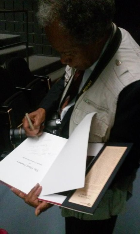 John H. White signs a photography collection at his presentation and chat in Novar Hall. Photo credit: Nia Norris